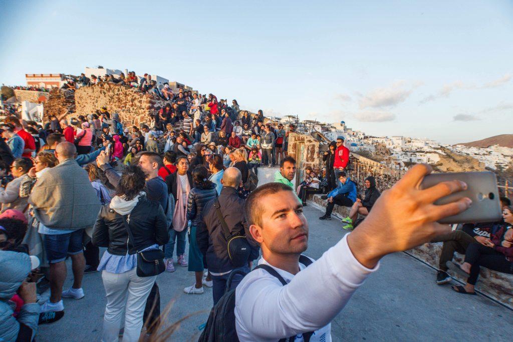Толпа людей на закате в Ойе